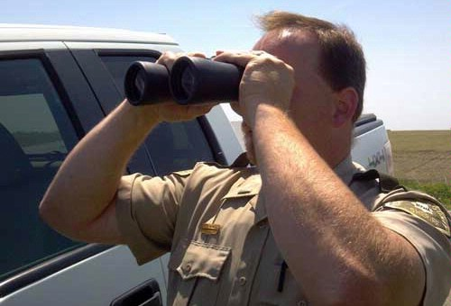 Law enforcement used binoculars to scan the fields
